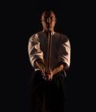 Il practicer Aikidoka di aikidi con una spada di legno di addestramento boken la foto scura del dojo fotografia stock libera da diritti