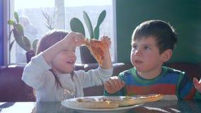 Il pranzo della famiglia, bambini sporchi mangia il pasto appetitoso nel ristorante della pizzeria vicino alla finestra video d archivio
