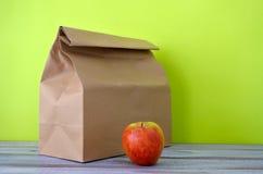 Il pranzo ha imballato in un sacco di carta marrone con la mela rossa Immagini Stock Libere da Diritti