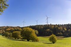 Il prato della collina della foresta di fonte di energia rinnovabile dei generatori eolici protegge immagini stock libere da diritti