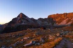 Il prato ed il pascolo alpini hanno messo in mezzo della catena montuosa di elevata altitudine ai tramonti Le alpi italiane, dest Fotografia Stock
