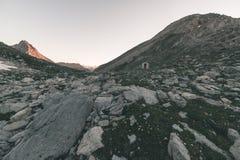 Il prato ed il pascolo alpini hanno messo in mezzo della catena montuosa di elevata altitudine ai tramonti Le alpi italiane, dest Immagine Stock Libera da Diritti
