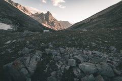 Il prato ed il pascolo alpini hanno messo in mezzo della catena montuosa di elevata altitudine ai tramonti Le alpi italiane, dest Fotografie Stock Libere da Diritti