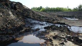 Il precedente rifiuto tossico dello scarico, natura di effetti da suolo contaminato ed acqua con i prodotti chimici e l'olio, amb stock footage