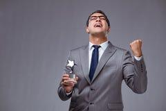 Il premio della stella della tenuta dell'uomo d'affari nel concetto di affari fotografie stock libere da diritti
