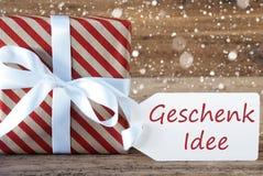 Il presente con i fiocchi di neve, testo Geschenk Idee significa l'idea del regalo Fotografie Stock Libere da Diritti