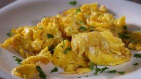 Il prezzemolo tagliato di diffusione sopra le uova rimescolate ha fritto dentro fuso su un piatto bianco video d archivio