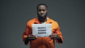 Il prigioniero maschio nero che tiene i diritti umani di rispetto firma in cellula, molestia sessuale video d archivio