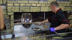 Il primo piano è un bicchiere di vino, cuoco unico del fondo mette la carne pronta sul piatto video d archivio