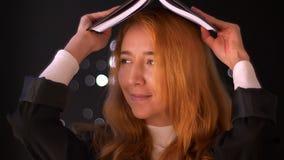 Il primo piano artistico sveglio del metraggio, donna caucasica dello zenzero è libro di lettura e poi fare io sono nel gesto del stock footage