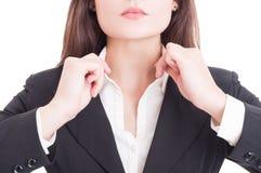 Il primo piano con la giovane donna di affari passa la regolazione del collare della camicia fotografia stock libera da diritti
