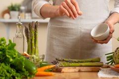Il primo piano, cuoco unico pulisce l'asparago, con le verdure su un fondo leggero Un concetto di alimento sano e sano di perdita fotografia stock libera da diritti