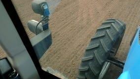 Il primo piano, dalla carrozza dell'autista uno del trattore può vedere la terra di recente arata del campo e di grande trattore stock footage