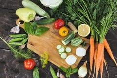 Il primo piano degli agricoltori freschi commercializza le verdure tagliate organiche coltivate sul posto su un tagliere Priorità Fotografia Stock Libera da Diritti