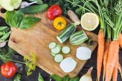 Il primo piano degli agricoltori freschi commercializza le verdure tagliate organiche coltivate sul posto su un tagliere Priorità Immagini Stock