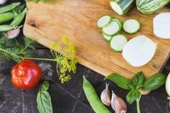 Il primo piano degli agricoltori freschi commercializza le verdure tagliate organiche coltivate sul posto su un tagliere Priorità Immagine Stock Libera da Diritti