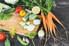 Il primo piano degli agricoltori freschi commercializza le verdure tagliate organiche coltivate sul posto su un tagliere Priorità Fotografie Stock Libere da Diritti