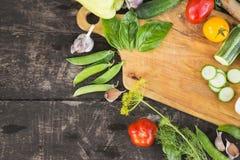 Il primo piano degli agricoltori freschi commercializza le verdure tagliate organiche coltivate sul posto su un tagliere Priorità Fotografia Stock