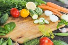 Il primo piano degli agricoltori freschi commercializza le verdure tagliate organiche coltivate sul posto su un tagliere Priorità Fotografie Stock