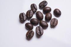 Il primo piano dei chicchi di caffè arrostiti ammucchia isolato su bianco studio Fotografie Stock