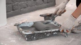 Il primo piano dei guanti d'uso della ragazza di una mano del ` s srotola un rullo di pittura archivi video