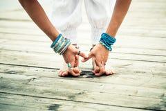 Il primo piano dei piedi scalzi della donna e le mani praticano l'yoga all'aperto immagini stock