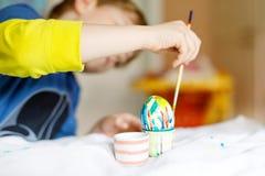 Il primo piano del bambino passa le uova di coloritura per la festa di Pasqua Fotografie Stock