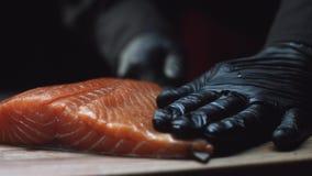 Il primo piano del cuoco unico di sushi in guanti affetta il salmone fresco alla barra di sushi Affettatura dei raccordi di color archivi video