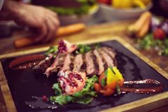 Il primo piano del cuoco unico passa la bistecca di manzo del servizio Fotografia Stock