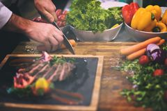 Il primo piano del cuoco unico passa la bistecca di manzo del servizio Fotografie Stock Libere da Diritti