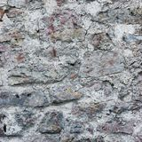 Il primo piano del fondo della parete di pietra, verticale ha intonacato il lerciume che il beige grigio rosso mette il bastone t fotografia stock libera da diritti
