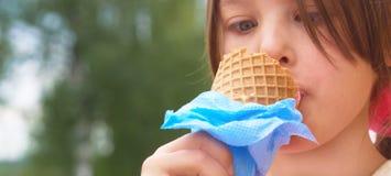 Il primo piano del gelato ha tenuto a disposizione dalla ragazza sveglia Piccola ragazza caucasica che mangia il gelato in un con fotografia stock libera da diritti