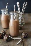 Il primo piano del latte al cioccolato e del dolce delle bottiglie schiocca Immagine Stock