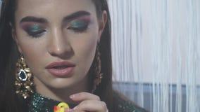 Il primo piano del modello di moda con trucco luminoso e la gomma duck archivi video