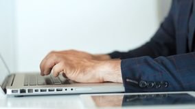 Il primo piano del ` s dell'uomo d'affari passa la battitura a macchina sul computer portatile in ufficio bianco archivi video
