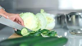 Il primo piano del ` s della donna passa il cetriolo di taglio in cucina stock footage