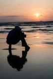 Il primo piano del tramonto dell'allerta del capo con la siluetta dell'uomo si siede sul beac Immagini Stock
