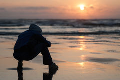 Il primo piano del tramonto dell'allerta del capo con la siluetta dell'uomo si siede sulla spiaggia Fotografia Stock Libera da Diritti