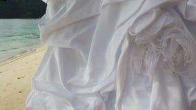 il primo piano del vestito da sposa bianco appende sull'albero verde video d archivio