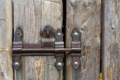 Il primo piano dell'acceso di da vecchio ruvido del sole fatto delle plance di legno alloggia il portone del granaio o della port Immagini Stock Libere da Diritti