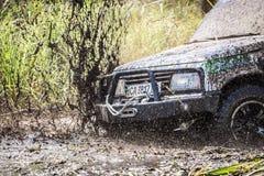 Il primo piano dell'automobile fuori strada sporca con spruzza di fango Fotografia Stock
