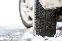 Il primo piano dell'automobile spinge dentro la gomma dell'inverno sulla strada nevosa Fotografia Stock