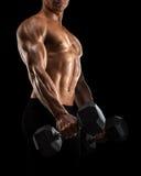Il primo piano dell'uomo atletico che pompa su muscles con la testa di legno Immagine Stock Libera da Diritti