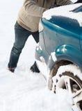 Il primo piano dell'uomo che spinge l'automobile ha attaccato in neve Immagini Stock