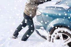 Il primo piano dell'uomo che spinge l'automobile ha attaccato in neve Fotografia Stock