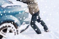 Il primo piano dell'uomo che spinge l'automobile ha attaccato in neve Fotografia Stock Libera da Diritti
