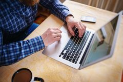 Il primo piano dell'uomo d'affari sta introducendo sul NET-libro portatile fotografia stock