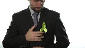 Il primo piano dell'uomo passa la tenuta del nastro giallo Consapevolezza del cancro alle ossa del sarcoma Concetto della medicin stock footage