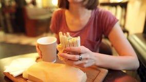 Il primo piano della donna affamata in vetri sta mangiando uno shawarma delizioso del pollo video d archivio