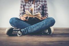 Il primo piano della donna dei pantaloni a vita bassa passa la tenuta che il libro aperto che si siede sopra corteggia Immagine Stock Libera da Diritti